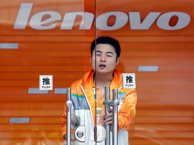 Ein chinesischer junger Mann öffnet eine Glastüre hinter der das Lenovo-Logo auf orangem Grund zu sehen ist.
