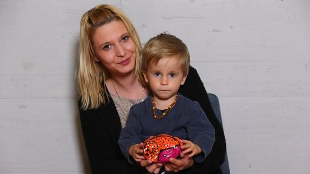 Eine junge Frau mit einem Kleinkind, das ein Stofftierchen in den Händen hält.