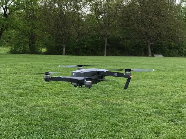 Drohne fliegt über einen Rasen