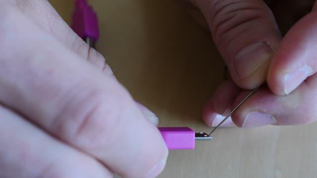 Mit einer herkömmlichen Nähnadel kann man zwei Noppen am Stecker zurückschieben.