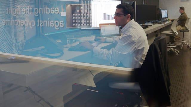 Zwei Männer sitzen in einem abgedunkelten Raum vor grossen Monitoren.