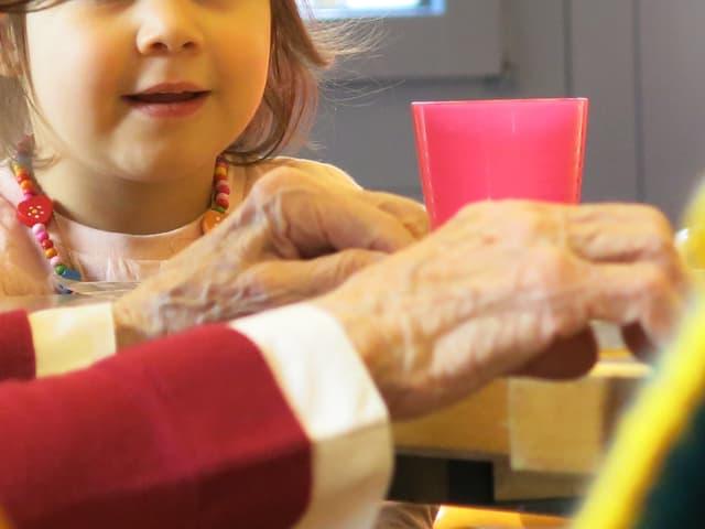 Ein Kind sitzt am Tisch. Davor eine alte Frau. man sieht deren Hände.