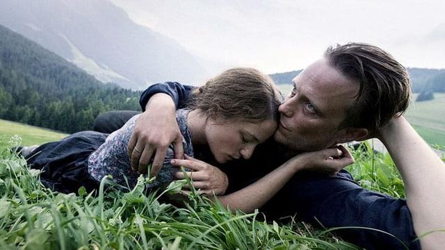 Ein Mann und eine Frau liegen in der Wiese und umarmen sich.