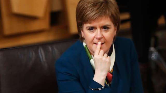 Sturgeon sitzt im Parlament, sie hält den Zeigefinger der rechten Hand an den Lippen.