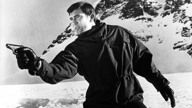 George Lazenby mit einem Revolver in den Schweizer Alpen.