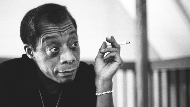 James Baldwin raucht eine Zigarette.