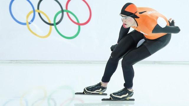 Eisschnellläuferin vor Olympia-Logo