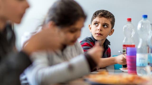 Kinder mit Migrationshintergrund beim Essen