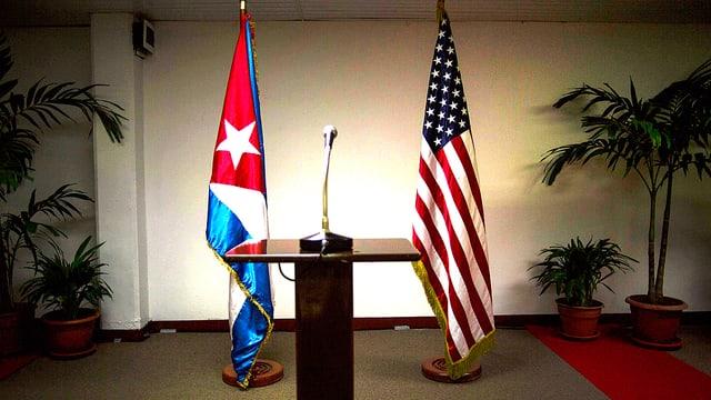 Die kubanische und die US-Flagge hinter einem spärlich beleuchteten Rednerpult.