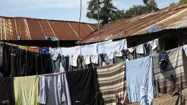 Gefüllte Wasserflaschen im Sonnenlicht auf Wellblechhütten im Nyalenda-Slum in Kisumu in Kenia.