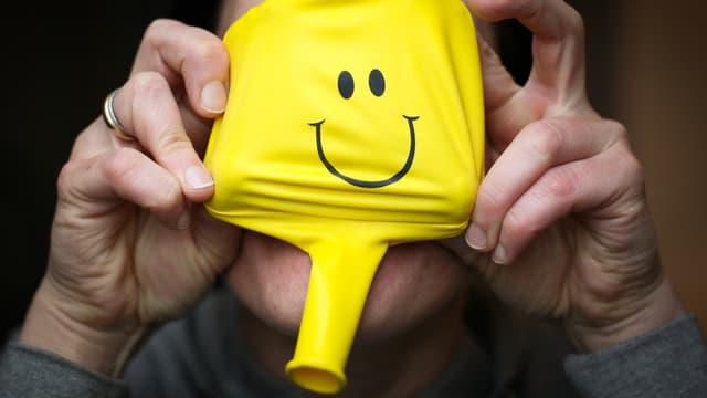 Eine Frau hält einen Ballon vor das Gesicht. Es ist ein gelber Ballon mit einem Smilie-Gesicht.