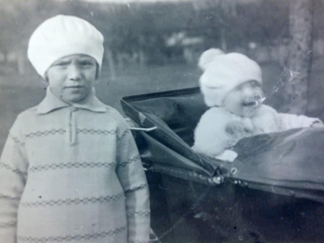 Ein kleines Mädchen mit Mütze steht neben einem Kinderwagen, indem ein Kleinkind sitzt.
