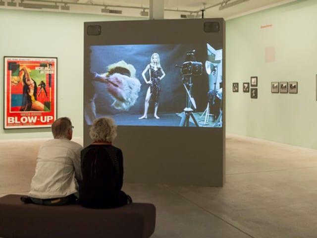 Zwei Besucher im Fotomuseum Winterthur vor einer Leinwand mit einem Filmstill.