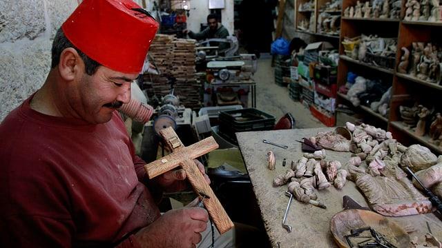 Ein Palästinenser schnitzt ein Kruzifix. Er verkauft seine Werke als Souvenirs an Touristen.