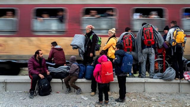 Eine Gruppe von Flüchtlingen mit Decken und Rucksäcken vor einem vorbeifahrendem Zug.