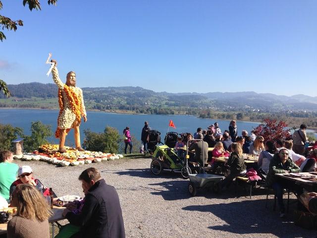 Besucher sitzen an Tischen, deneben eine Zeus-Statue aus Kürbis, dahinter die Aussicht auf den Pfäffikersee.