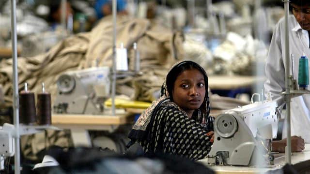 Eine Bangladeshi sitzt inmitten von Stoffbergen vor einer Nähmaschine.