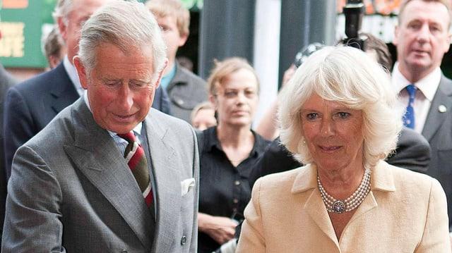 Charles und Camilla durchschneiden ein Band.
