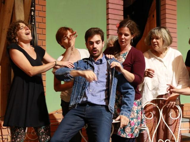 Mehrere Frauen stehen rund um die beiden Darsteller herum und singen.