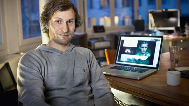 Ein junger Mann sitzt am Schreibtisch und kehrt sich der Kamera zu. Er trägt einen grauen Pullover. Auf dem Tisch steht ein Laptop.