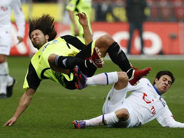 Ein Fussballer grätscht einen anderen, der durch die Luft fliegt mit wehenden langen Haaren.