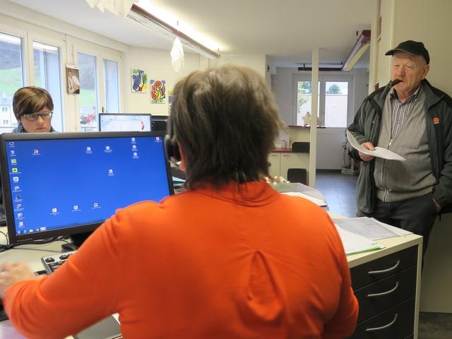 Eine Frau sitzt in einem Büro an einem Computer.