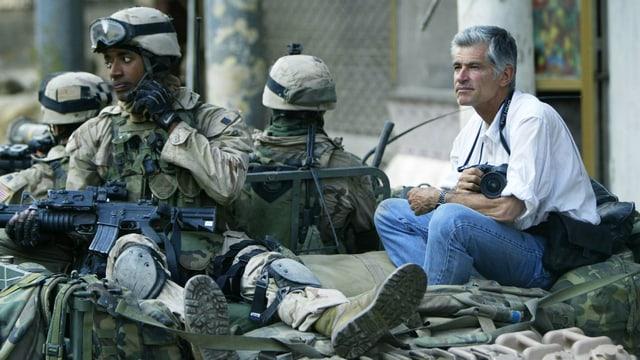 Kriegsfotograf James Nachtwey sitzt mit seiner Kamera neben Soldaten.