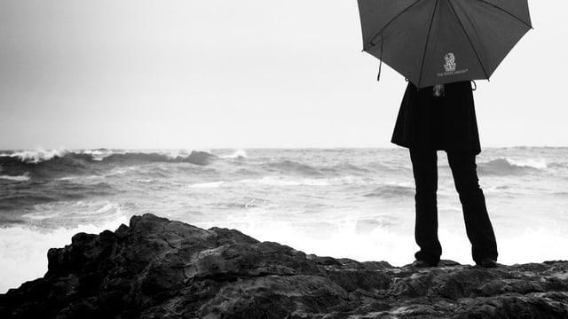 Ein Mensch blickt im Schutze eines Regenschirms auf die stürmische See.