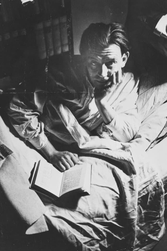 Friedrich Glauser liegt auf dem Bett mit einem Buch. Er stützt seinen Kopf.