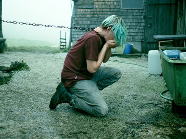 Ein Jugendlich hat eine Kette am Hals. Er ist in einer ländlichen Umgebung.