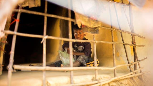 Ein Junge sitzt hinter einem Gitter.