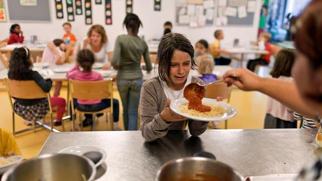 """Im Hort """"In der Ey"""" in der Stadt Zürich erhält ein Kind gerade Spaghetti geschöpft."""