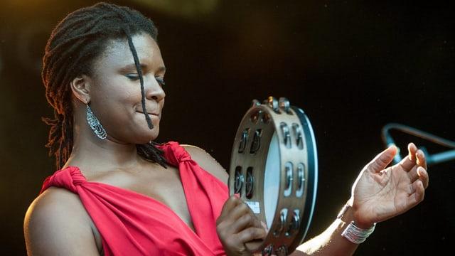 Eine Frau hat ein Tambourin in der Hand.