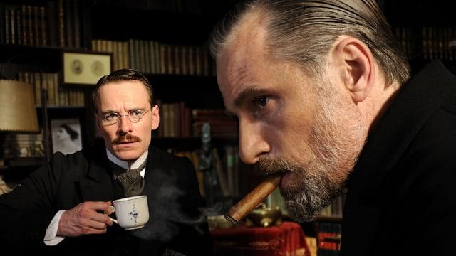 Jung im Hintergrund mit einer Teetasse, vorne Freud mit Zigarre.