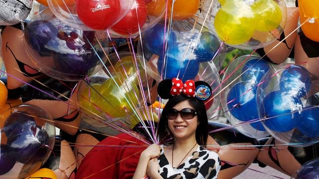 Junge Frau hält Ballone mit Aufschrift «Disneyland Hong Kong» in der Hand.