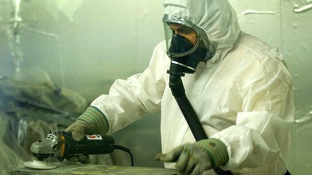 Ein in Schutzkleidung gehüllter Arbeiter schleift ein asbestverseuchtes Werkstück.