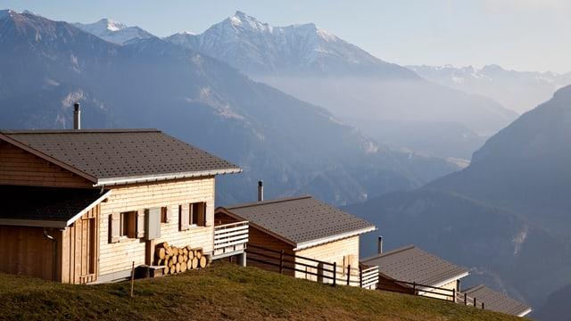 Drei Holzhäuser auf einer Bergkuppe. Im Hintergrund Berge.