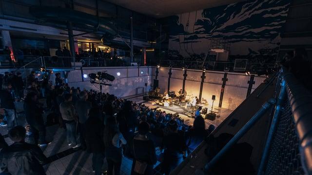 Band mit Publikum. Band spielt in einem ehemaligen Hallenband mit weissen Kacheln.