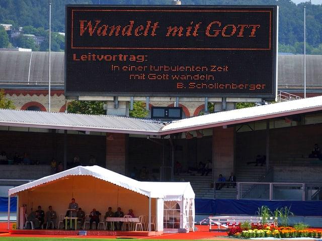 Ein Zelt steht in einem Fussballstadion, über dem eine Grossleinwand mit der Aufschrift «Wandelt mit Gott» steht.