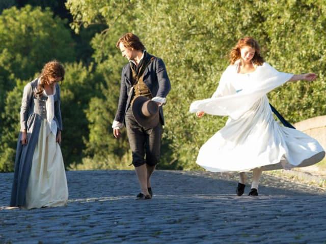 Ein Mann zwischen zwei Frauen, eine mit einem langen weissen Kleid.