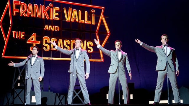 Vier Männer in grauen Anzügen stehen mit ausgestreckten Armen auf einer Bühne und singen.