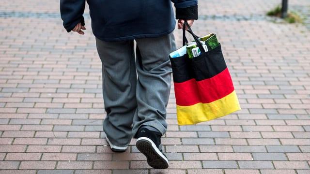 Ein Mann trägt einen Beutel in der Farbe der Deutschland-Flagge, der von der AfD verteilt wurde.