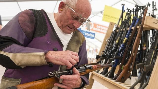 Mann mit Gewehr vor Gewehrständer