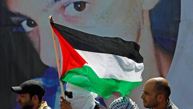 Demonstranten mit Fahne vor Foto des Getöteten