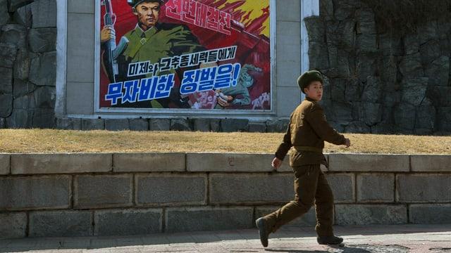 Ein nordkoreanischer Soldat vor einem Propaganda-Plakat.