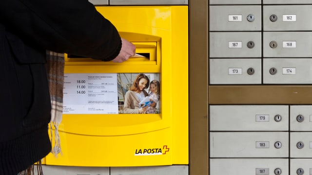 Ein Kunde wirft einer Poststelle in Massagno (TI) einen Brief in den Briefkasten. (keystone)
