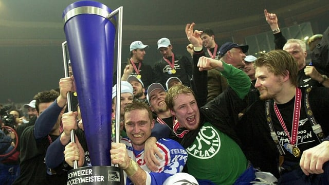 Eine Mannschaft von Hockey-Spielern jubelt, in der Bildmitte ein blauer Pokal und ein schreiender Mathias Seger.