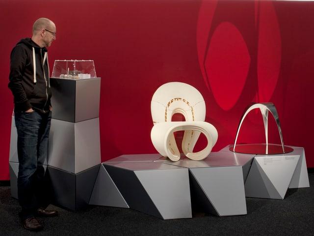 Besucher in der Ausstellung vor weissem Design-objekt vor rotbemalter Wand.