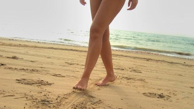Am Strand malt eine Frau mit ihren Füssen Spuren in den Sand.