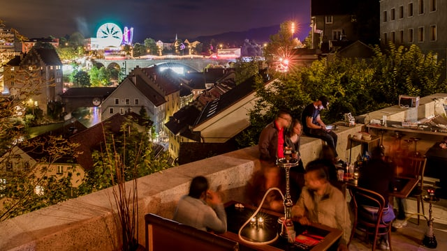 Menschen sitzen an Tischen auf einer Terrasse über einer Stadt.